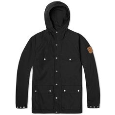 Fjällräven Greenland Jacket Black - Utilising their famous water-resistant G-1000® fabric, the Fjallraven Greenland jacket is one of brand's most popular creations. Originally designed in 1968 when company founder Åke Nordin discovered a need for durable functional jackets after a Swedish expedition. The jacket features two way zip fastening blind behind a snap placket, two front pockets & two chest pockets all with snap closure & a high stance hood, with arctic fox branding to the left arm