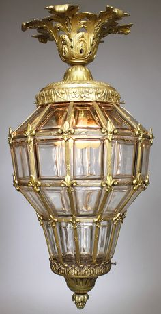 "A French Early Century Gilt-Metal Paneled Beveled Glass ""Versailles"" Style Hanging Twin-Light Lantern. The elongated body topped with a crown-shaped design among floral shields. The gilt-brass sectional panel lining surmounted with flower buttons. Bubble Chandelier, Chandelier Pendant Lights, Crystal Chandeliers, Hanging Lanterns, Hanging Lights, Versailles, Art Deco Lamps, Metal Panels, Antique Lamps"