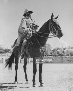His Imperial Majesty Emperor Haile Selassie I of Ethiopia on horseback. He is wearing a solar topee and a cloak.