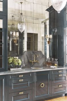 medium dark grey cabinetry and antique mirror tiles with trendy pendant light.  Chinese brass pulls.  Transitional decorating. DesignNashville.com home accents