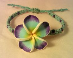 This handmade bracelet is made from dyed sky blue hemp, with purple chrome E beads, and a large polymer plumeria bead. It has an adjustable