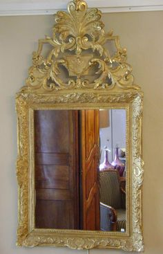 Large mirror in #giltwood with #pediment. Richly #decorated with scrolls and foliage. #Regency, early 18th century. For sale on Proantic by Antiquités Alric.