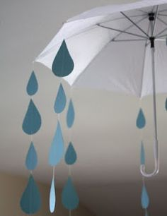 Baby shower theme. Umbrella with raindrops taped to fishing wire.