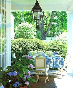 Columns, brick floor, lantern, hydrangeas, blue and white table - Carolyne Roehm