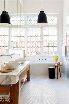 Bathroom with clear stained glass windows, simple white tile, and an industrial pendant light
