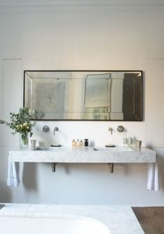bathroom ~ an antique mirror, grey Carrera marble, double sinks & wall mounted fixtures