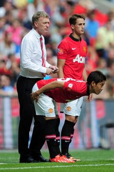 Manchester United manager David Moyes looks on as Adnan Januzaj (R) and Shinji Kagawa of Manchester United await their substitution