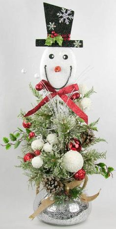 A cute snowman face with a black hat and glittered red bow tie sits in snowy braches, snowballs, pine cones and red ornaments. This arrangement is made in a painted pressed metallic glass bell shaped