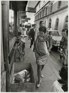 A woman passes a boy sleeping in a box on the streets of San Salvador. 1970's photo by Cornell Capa