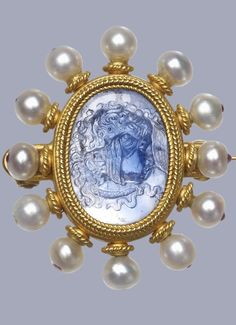 A brooch set in gold with a central sapphire cameo head of Medusa in a heavy ropework setting bordered with pearls, each pinned to a stem decorated with ropework. The pins are stopped at the outer edge with minute cabochon rubies. The setting is marked on the reverse with the maker's mark in applied wirework and an engraved monogram on the back of the cameo, 1870 (circa) Workshop of: Castellani.