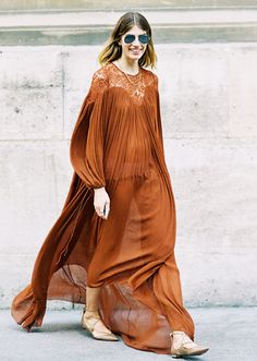 Veronika Heilbrunner wears a muted orange maxi dress with lace-up flats and aviator sunglasses