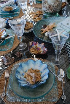 A very attractive sea-themed table.  I love the scallop-shaped dishes.  What's in them?  Brown sugar and real shells?  The mix of colored and clear glass with basketry mats (and brown shells) is just right.
