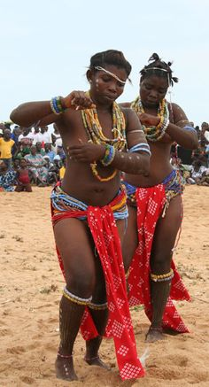 Two Krobo women in initiation dress and dancing at a festival