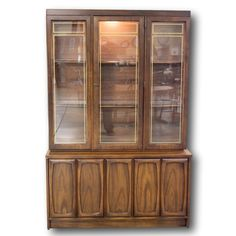 Mid-Century Modern china cabinet features a dark finish, glass doors with gold trim, fixed glass shelves with plate grooves and wooden trim, and a lighted interior.