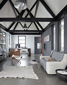 A modern rustic new built warehouse that softens it's industrial edges with beautiful rugs, throws and cushions in boiled wool and felt.