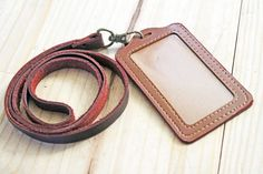 Handmade lanyard that is made with a very soft brown saddle string leather that measures 1/2 inch wide. Lanyard has an antiqued brass swivel
