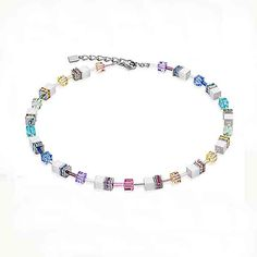 Swarovski® Crystals with rhinestone rondelles, synthetic solid coloured tiger's eye and polaris with fine glass cylinders and stainless steel. A unique twist to the classic Geo Cube featuring fresh colours contrasted against white.