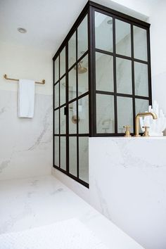 This West Hollywood Bath Makeover is luxurious with the grid glass shower enclosure and marble walls.