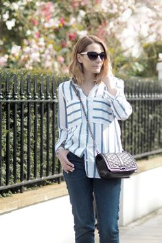 Simple casual outfit, striped blue and white shirt with quilted designer bag and jeans