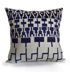 Navy blue Aztec throw pillow on white linen. This versatile accent pillow has an embroidered Aztec pattern with a tribal theme. The Aztec decorative pillow covers are very on trend and this pattern in