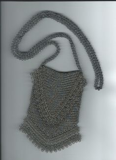 Brass and Steel Chainmaille Purse. It has a lacy Fringe on both the Flap and the bottom of the Bag.