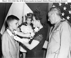 Mrs. Howard W. Gilmore placing her late husband's Medal of Honor around the neck of her son, Howard Jr., during the presentation ceremony on 18 August 1943. Standing by are Gilmore's daughter, Vernon Jeanne, and Rear Admiral Andrew C. Bennett.