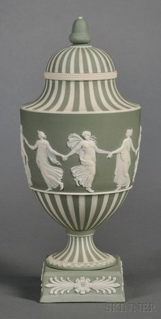 Wedgwood Green Jasper Dip Dancing Hours Vase and Cover, England, early 20th century, acorn finial, the central band of classical figures bordered with vertical engine turnings, mounted on a raised square plinth.