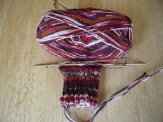 Work in Progress (WIP) - a knitted sock partially done on Double Pointed Needles (DPNs) using variegated sock yarn.
