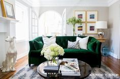 A white porcelain Dalmatian statue sits in front of a white fireplace topped with a gold leaf print and facing a black cocktail table positioned on a black leaf print rug in front of an emerald green velvet tufted sofa topped with white pillows.