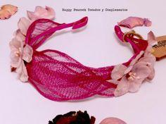 Diadema forrada en raso magenta con hojas en el mismo tono cosidas y aplicaciones de flores de terciopleo en malva.
