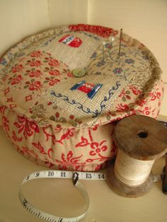piecework and embroidery on a pincushion with a corded edge