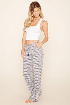 A pair of pajama pants featuring a checkered floral print, an elasticized waist, a tasseled self-tie waist, and slanted front pockets.