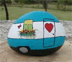 Add a little wanderlust to your gaden with a hand painted vintage travel trailer rock decor.