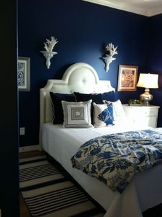 Navy blue walls make a dramatic backdrop for a white, upholstered headboard in this bedroom. With the presence of blue and white textiles, the room boasts tons of comfort and classic style.