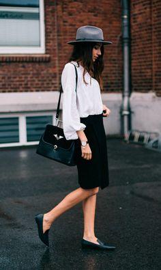 Street style look com camisa branca, saia social, chapéu e sapatilha.