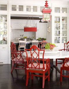 "White Kitchen with Red and Black Accents. Bold strokes of red add charisma to a white kitchen outlined in black. Red lacquered Italian armchairs, a red hanging ""pineapple"" lantern above the table, and a red ""Gothic"" lantern above the island contribute to the overall exuberance of the room."