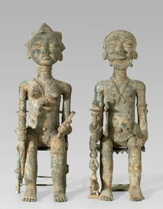 A Baule Bronze couple found in the ground of an abonened house South-East of Bouaké man and woman seated on stools of the regional style, holding in their hands the Akan-style regalia of the Baule nobleman, man and woman with louncloths and necklaces, the woman with the traditional coiffure of the 18 - 19 century hairstyle of a high ranking personality, the man wearing a stylized goatee; various coloured patina, greenish, occre up to orange, with remnants of encrusted earth.