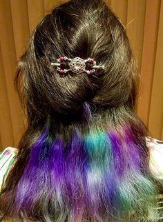 A flexi clip securing a half up style in peek-a-boo unicorn rainbow hair.