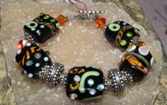 This bracelet was made with  Large Black and Orange  lampwork beads,   swarovski Crystal Elements,quality plated silver bead caps,quality plated silver plated type toggle clasp .. This measures about