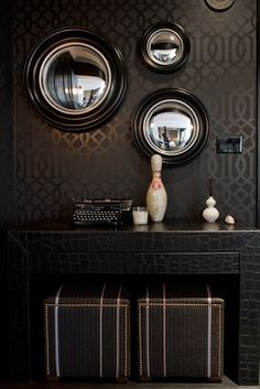 The Wall in the Hall ~ Dark and masculine interior with damask patterned wallpaper, a triple hit of 'fish eyed' mirrors, vintage decor with 2 leather stools with nail studded detailing tucked under the console....exotically gorgeous.