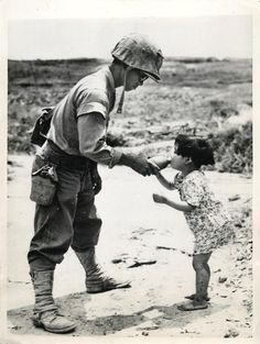 1945- Tiny Japanese girl drinks from the canteen of a U.S. Marine who found her in a cave on Okinawa.