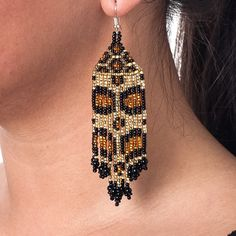 These earrings are made of beautifully colored Czechoslovakian glass beads handcrafted into a jaguar pattern. With 13 strands that give the earrings movement, these earrings secure with shepherd hooks.