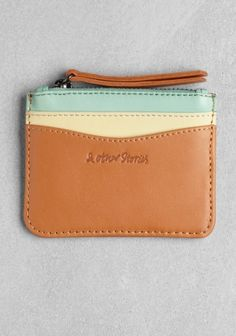 & OTHER STORIES Made from soft tricolor leather, this wallet has a zipped pocket with cotton twill lining and two card pockets on the front. The zip pull has a long leather tassel. Dimensions: 10 x 8 cm.
