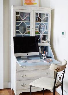 A white and black French desk chair sits in front of a white French secretary desk accented with a blue interior and fitted with a pull down desk top and glass front cabinets.