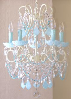 """5-Light Ivory Beaded Chandelier with Opal Aqua Blue Crystals by A Vintage RoomThis lovely, vintage-inspired 5-light chandelier is finished in ivory and features Milky Opal Aqua French pendants and matching fancy-cut glass bobeches. Crystal teardrops and layers of crystal chain swags add glam and sparkle, and delicate glass bead chains in sea blue add just the right amount of color. This chandelier measures 17"""" wide across the arms and 23"""" down to the crystal ball. This chandelier will come…"""