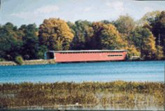 The Langley Bridge, longest  covered bridge in MI & one of the longest in the nation at 282 ft over the St Joseph River near Centreville. Named for Thomas Langley, Centreville's first settler,1831. Built in 1887 by Pierce Bodner of nearby Parkville,using the Howe truss system. 3 spans, 94 ft long ea. 16 ft high and 19 ft wide. Despite being raised 8 ft during construction of Sturgis Dam in 1910, it still sits unusually low for a river crossing. Its longevity is a small miracle.