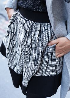 Black, white, and gray. Make the most of your monochromatic look by mixing a textured sweater, patterned skirt, and long wool jacket   Banana Republic