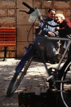 An old couple in love on a public bench