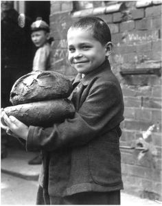 'Boy holding daily bread ration of two loaves for six people' by John Vachon, 1947  #Expo2015 #Milan #WorldsFair