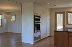 Modern kitchen; stainless steel appliances, wood floor, natural light